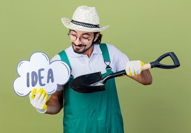 Jeune homme de jardinier barbu portant une combinaison et un chapeau tenant une pelle et un signe de bulle de discours avec une idée de mot en le regardant souriant debout sur un mur vert clair