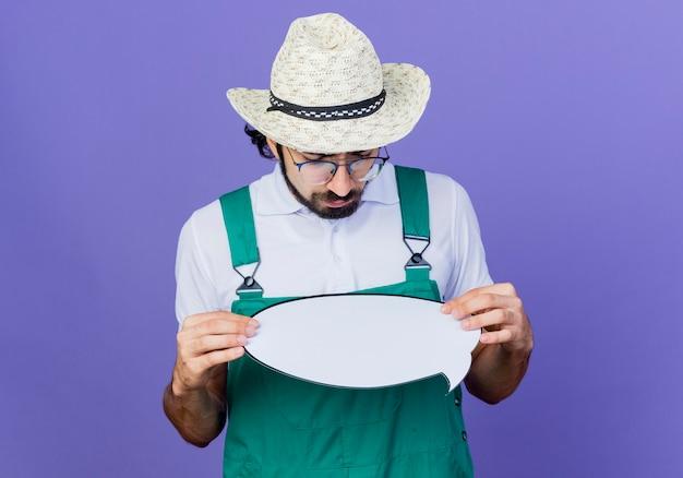 Jeune homme de jardinier barbu portant une combinaison et un chapeau tenant un signe de bulle de dialogue vide en le regardant avec un visage sérieux debout sur un mur bleu