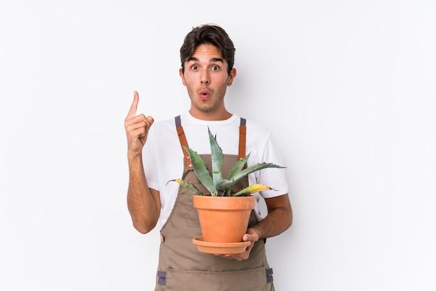 Jeune homme jardinier caucasien tenant une plante isolée ayant une excellente idée, concept de créativité.