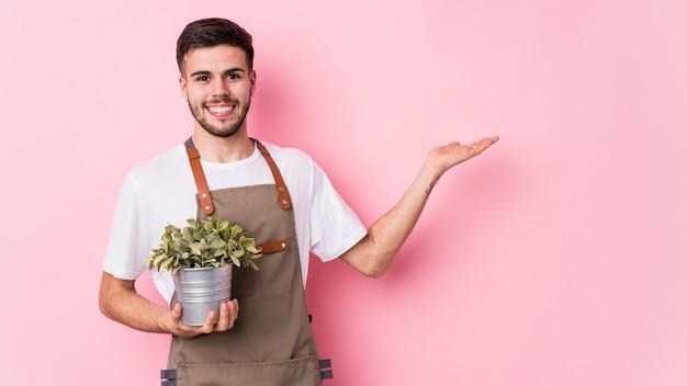Jeune homme de jardinier caucasien tenant une plante isolée montrant un espace de copie sur une paume et tenant une autre main sur la taille.