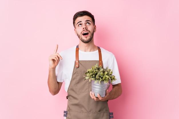 Jeune homme jardinier caucasien tenant une plante isolée pointant à l'envers avec la bouche ouverte.