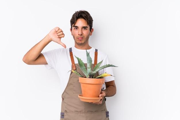Jeune homme jardinier caucasien tenant une plante montrant un geste d'aversion, les pouces vers le bas.