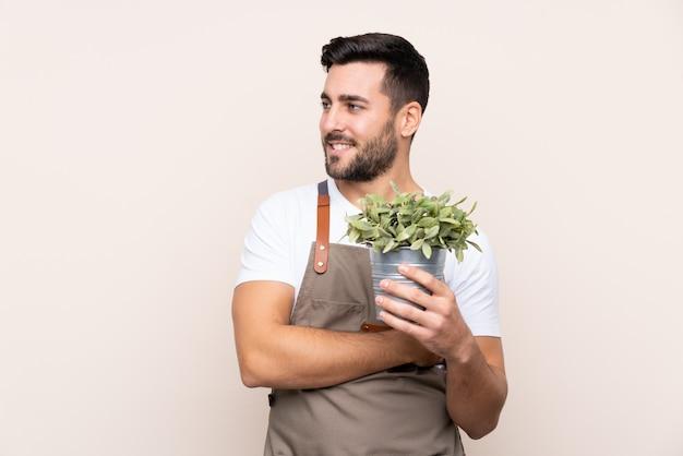 Jeune homme jardinier sur mur isolé