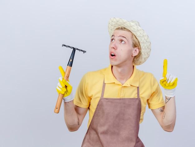 Jeune homme jardinier portant une combinaison et un chapeau dans des gants en caoutchouc tenant un mini râteau pointant avec un index figner jusqu'à être surpris