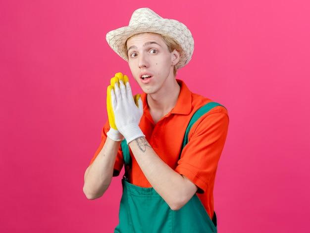 Jeune homme de jardinier portant combinaison et chapeau dans des gants en caoutchouc tenant les paumes ensemble