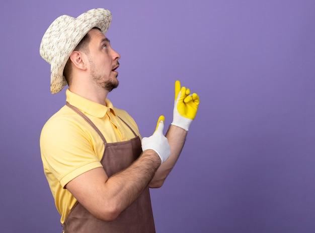 Jeune homme de jardinier portant combinaison et chapeau en gants de travail pointant avec index figners retour à la surprise