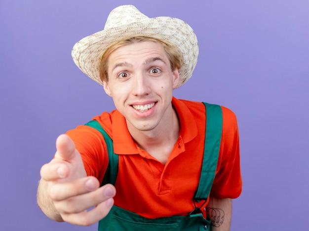 Jeune homme de jardinier portant combinaison et chapeau regardant la caméra en souriant avec le bras comme demandant debout sur fond violet