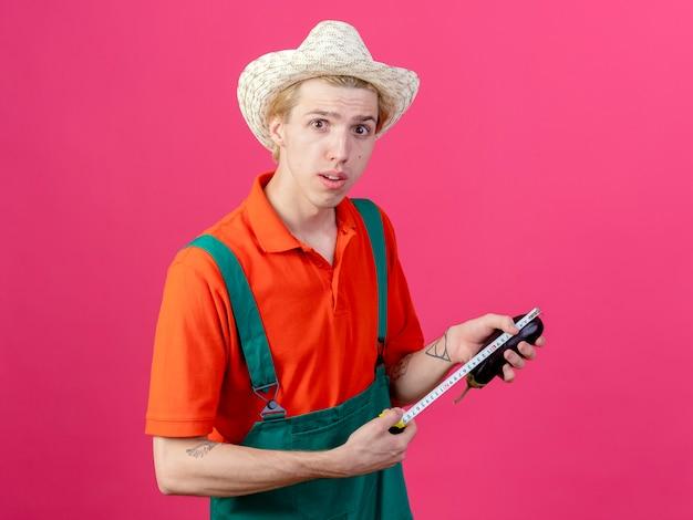 Jeune homme de jardinier portant combinaison et chapeau tenant l'aubergine en le mesurant