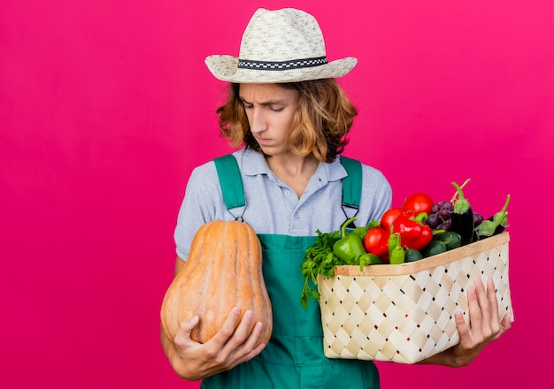 Jeune homme de jardinier portant une combinaison et un chapeau tenant une caisse pleine de légumes frais
