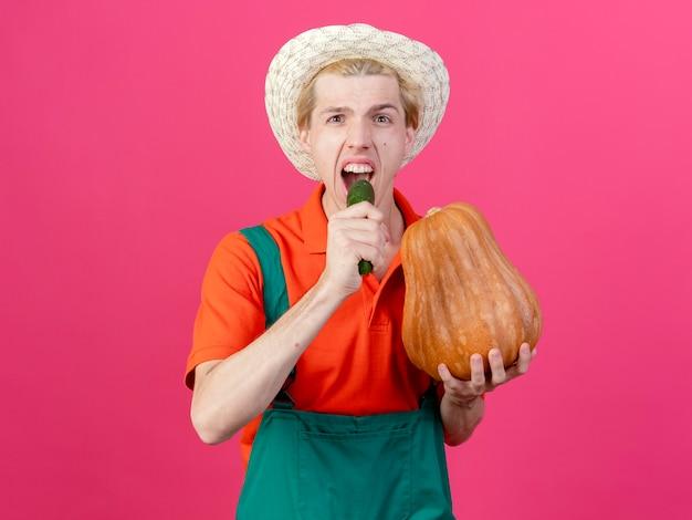 Jeune homme de jardinier portant combinaison et chapeau tenant la citrouille et le concombre