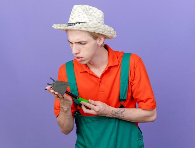 Jeune homme de jardinier portant combinaison et chapeau tenant mattock le regardant intrigué debout sur fond violet