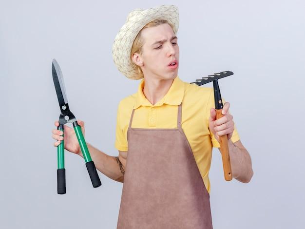 Jeune homme jardinier portant une combinaison et un chapeau tenant un mini râteau et un coupe-haie regardant un râteau intrigué