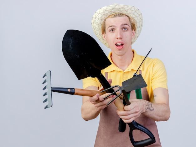 Jeune homme jardinier portant une combinaison et un chapeau tenant un râteau à pioche et un coupe-haie surpris