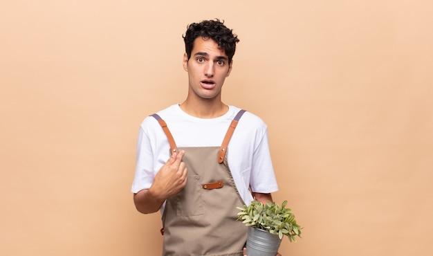 Jeune homme jardinier semblant choqué et surpris avec la bouche grande ouverte, pointant vers soi