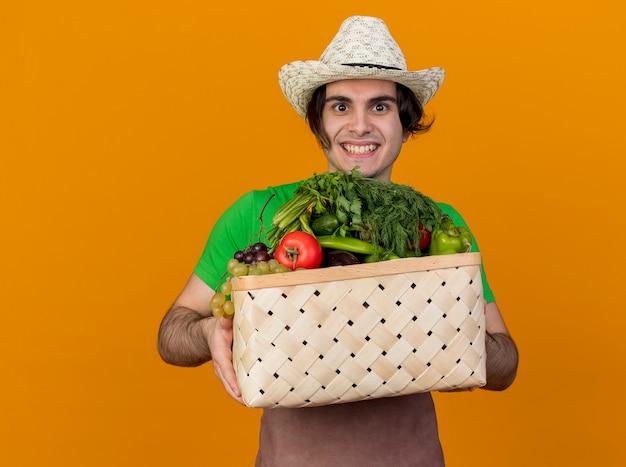 Jeune homme jardinier en tablier et chapeau tenant une caisse pleine de légumes regardant la caméra en souriant avec un visage heureux debout sur fond orange