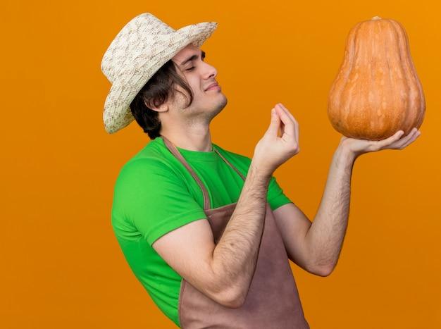 Jeune homme de jardinier en tablier et chapeau tenant la citrouille en le regardant faire un excellent chanter avec les doigts heureux et heureux debout sur un mur orange