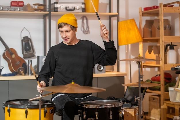 Jeune homme en jean noir, sweat-shirt et bonnet jaune tenant des baguettes au-dessus de la batterie