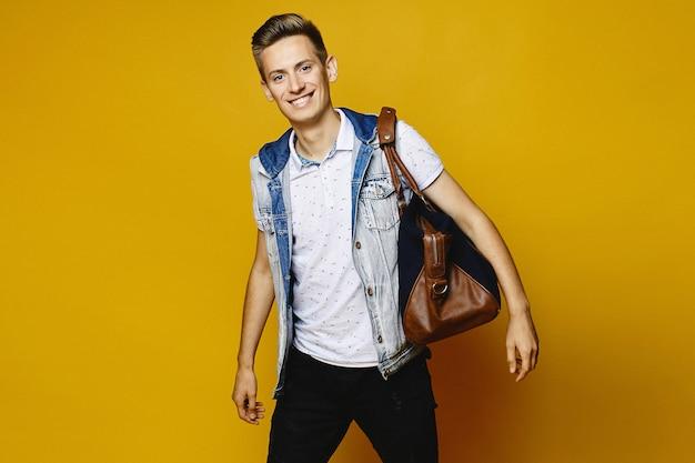 Un jeune homme en jean prépare sa valise de voyage pour la remettre dans les bagages, isolée au mur jaune.
