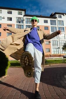 Un jeune homme en jeans, chaussures kaki. dans un saut, jette sa jambe en avant, donne des coups de pied, comme une matrice