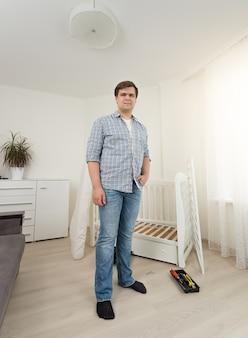 Jeune homme en jeans et chemise posant dans la chambre avec des meubles démontés