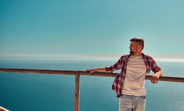 Un jeune homme en jeans et chemise se tient près d'une clôture en bois au sommet d'un rocher sur fond de mer.