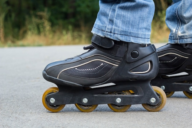 Jeune homme en jeans, équitation patins à roulettes dans la ville. bouchent les jambes