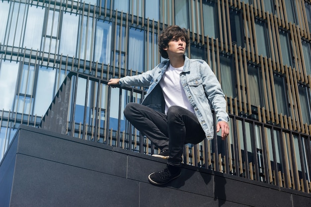 Jeune homme en jeans faisant du parkour et des cascades dans la ville