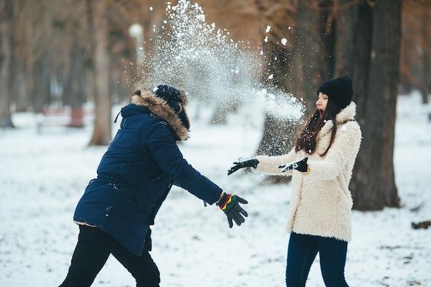 Jeune homme jetant une boule de neige à son ami