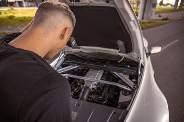 Jeune homme jetant un œil à son moteur de voiture avec le capot sauté