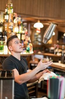 Jeune homme jetant un shaker à cocktail