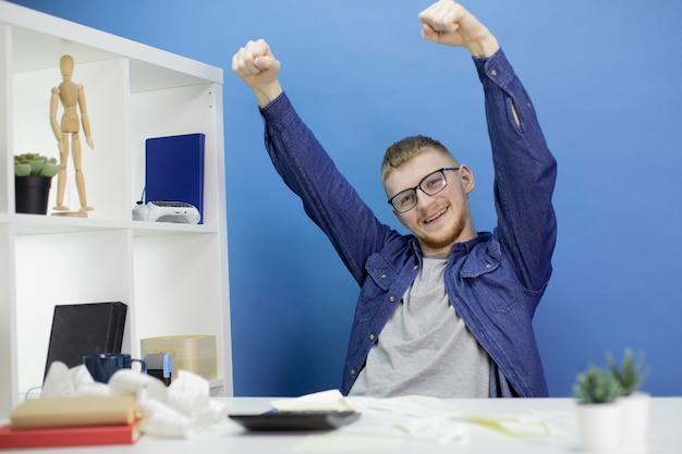 Jeune homme jette volontiers ses mains sur la calculatrice du budget national et les reçus