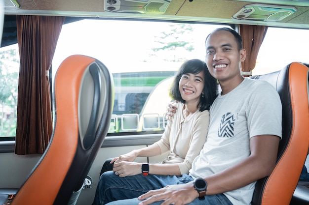 Un jeune homme et une jeune femme sourient alors qu'ils sont assis côte à côte dans un siège d'autobus lors d'un voyage
