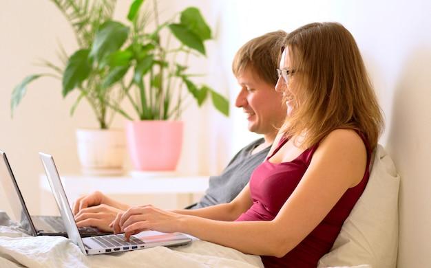 Un jeune homme et une jeune femme travaillant dans la chambre à coucher sur un ordinateur portable