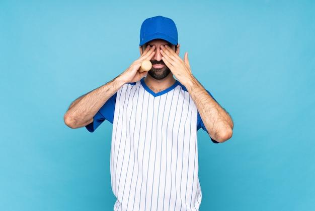 Jeune homme jouant au baseball sur bleu isolé couvrant les yeux par les mains