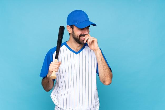 Jeune homme jouant au baseball sur mur bleu isolé souriant beaucoup