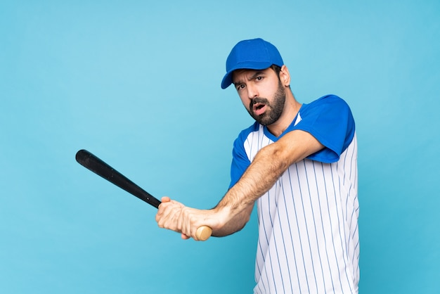 Jeune homme jouant au baseball sur mur bleu isolé