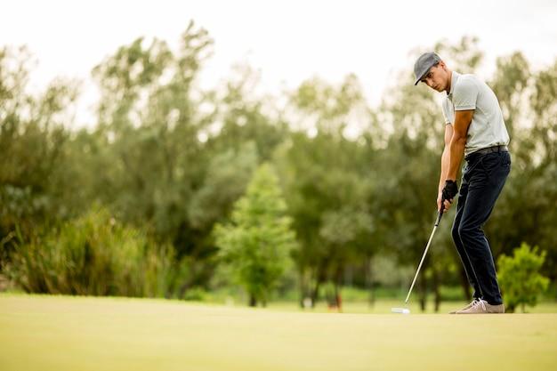 Jeune homme jouant au golf sur le parcours de golf