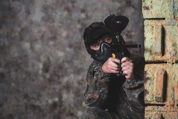 Jeune homme jouant au jeu de bataille de paintball avec ses amis, portant un masque de camouflage et de protection, une bannière, une activité de loisirs