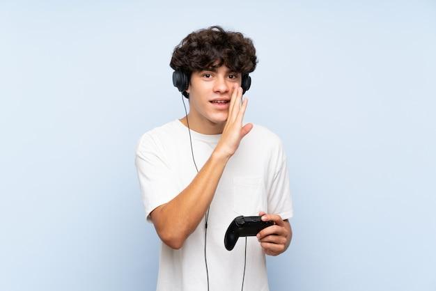 Jeune homme jouant avec un contrôleur de jeu vidéo sur mur bleu isolé chuchotant quelque chose