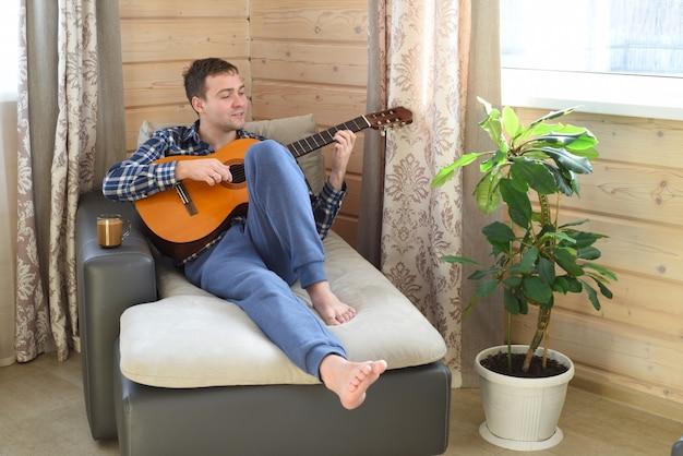 Jeune homme jouant de la guitare et assis sur un canapé