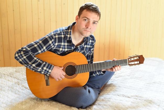 Jeune homme jouant de la guitare et assis sur un lit