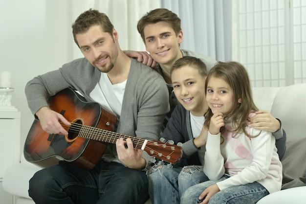 Jeune homme jouant de la guitare pour sa famille