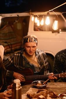 Jeune homme jouant de la guitare pour ses amis alors qu'ils étaient assis à table pendant le camping dans la forêt