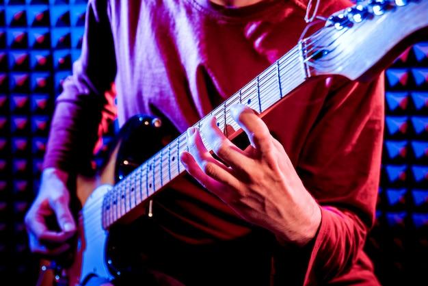 Jeune homme jouant de la guitare en studio d'enregistrement sonore.