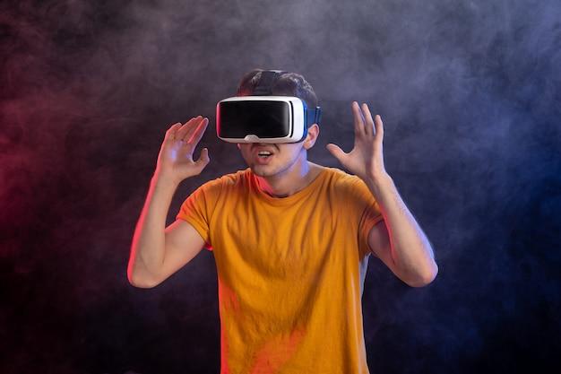Jeune homme jouant à un jeu effrayant en surface sombre de réalité virtuelle
