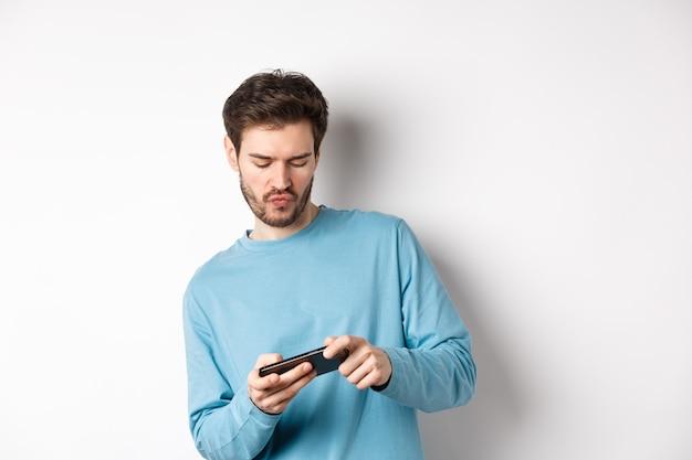 Jeune homme jouant à des jeux vidéo sur smartphone, inclinez le corps et appuyez sur l'écran mobile, debout joyeux sur fond blanc.