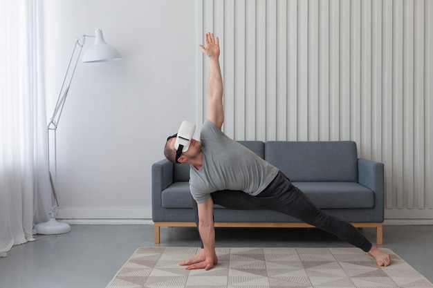 Jeune homme jouant à des jeux vidéo tout en portant des lunettes de réalité virtuelle