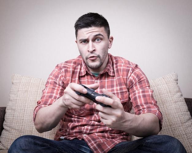 Jeune homme jouant à des jeux vidéo