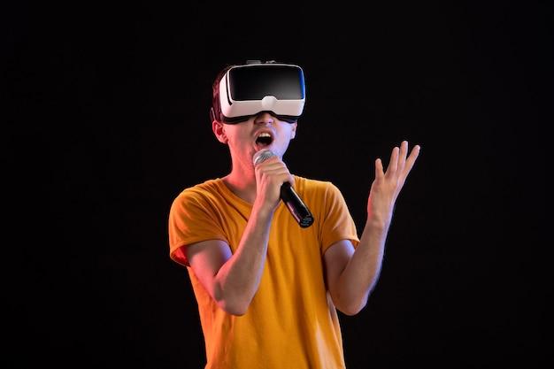 Jeune homme jouant à la réalité virtuelle et chantant sur dark desk vision gaming tech visual d
