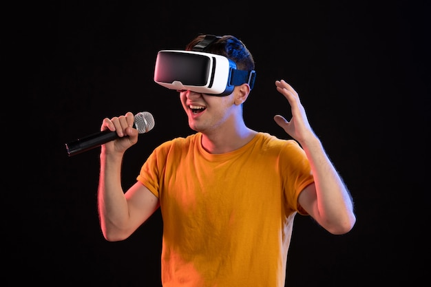 Jeune homme jouant à la réalité virtuelle et chantant sur la surface sombre
